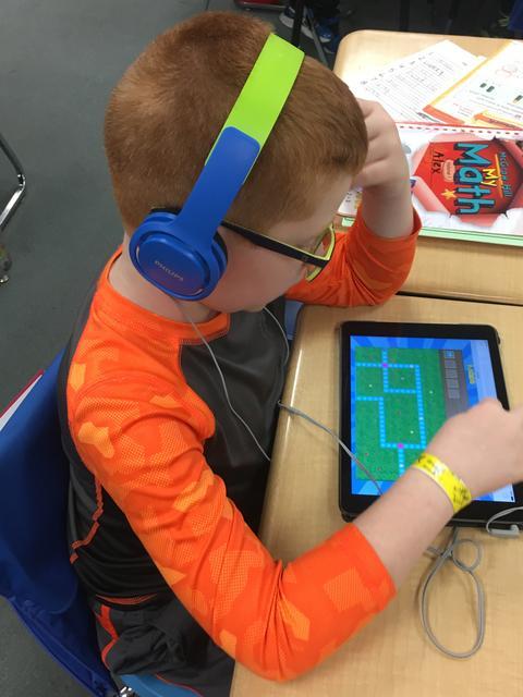 boy coding on an ipad
