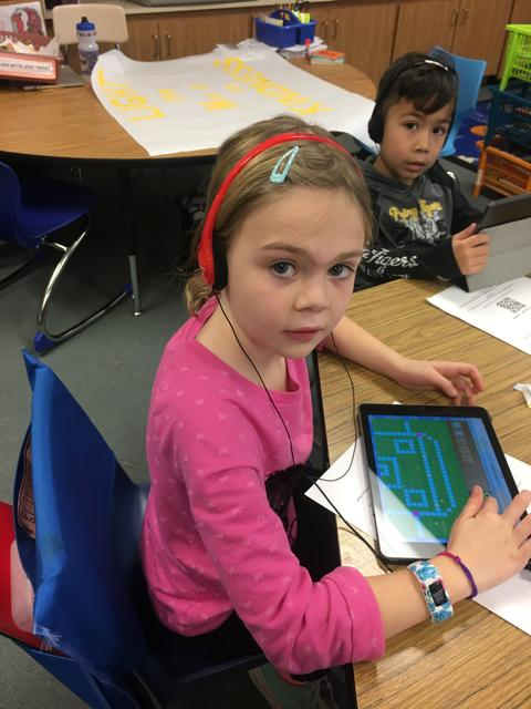 girl looking at camera while holding her ipad