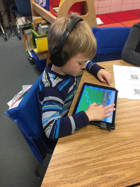boy coding using the ipad touch screen