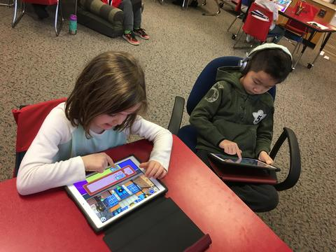 a boy and a girl using ipads to code