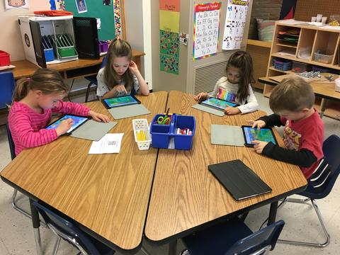 four students around a table using ipads to code