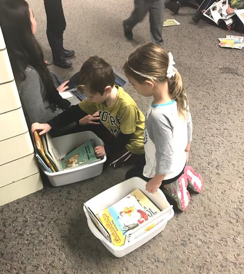 Two students kneeling on the floor looking through tubs of books