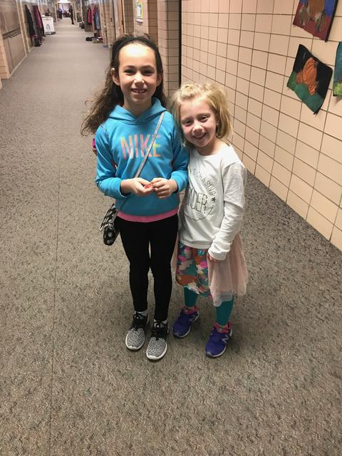 Two girls posing for picture in school hallway