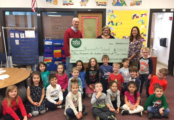 Principal, parents and students holding large check from Whole Foods