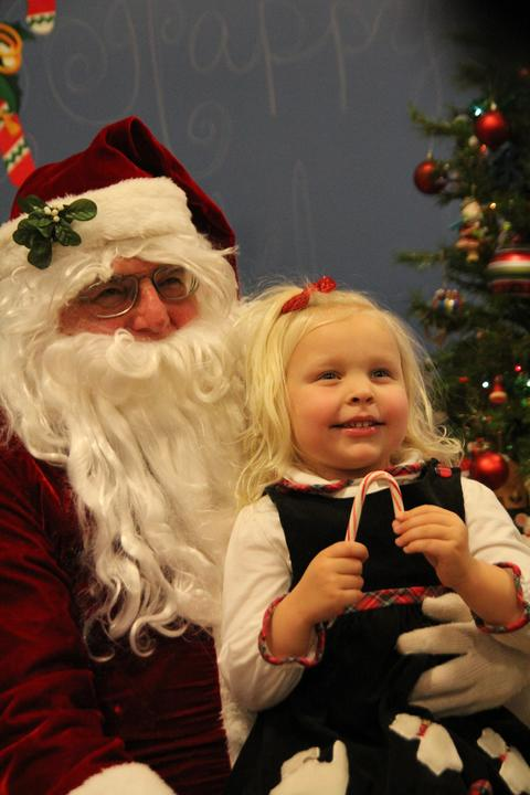 girl with candy cane on santa's lap