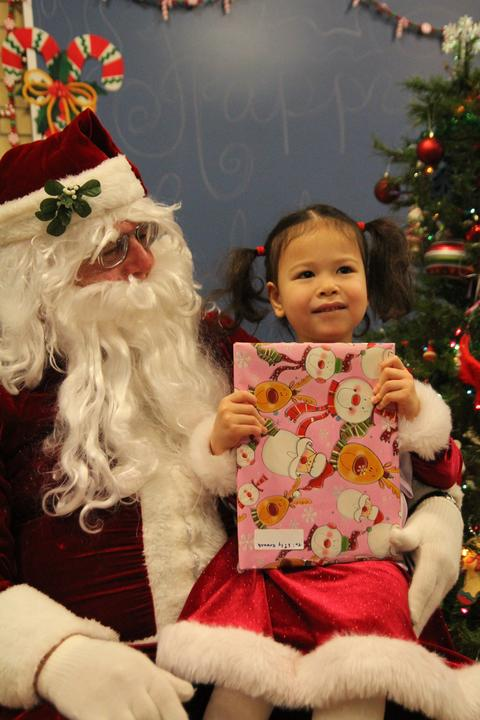 girl on santa's lap with pink gift