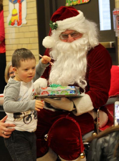 santa holding present for boy