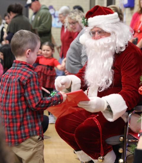 santa helping boy open gift