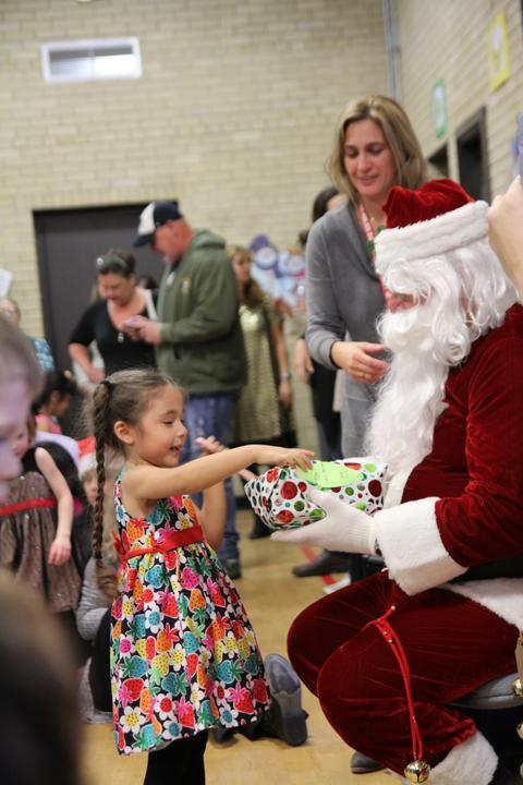 girl excitedly opening gift with santa