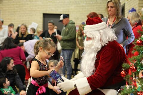 girl opening her gift with santa