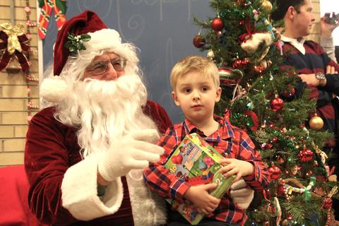 boy holding gift and posing with santa
