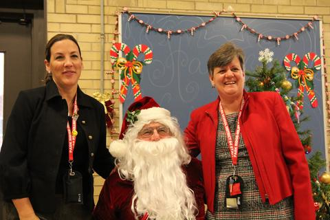 superintendent, principal and santa smiling for picutre