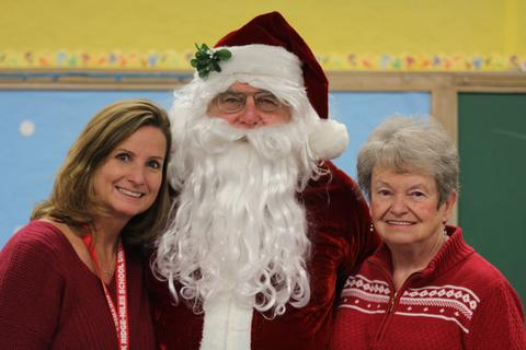 staff member with santa and mrs. claus