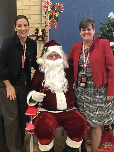 Superintendent, Principal and Santa smiling for picture