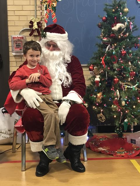 boy smiling while sitting on santa's lap