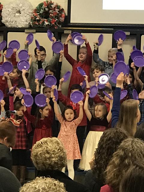 Students at Holiday Sing waving purple plates as part of their performance