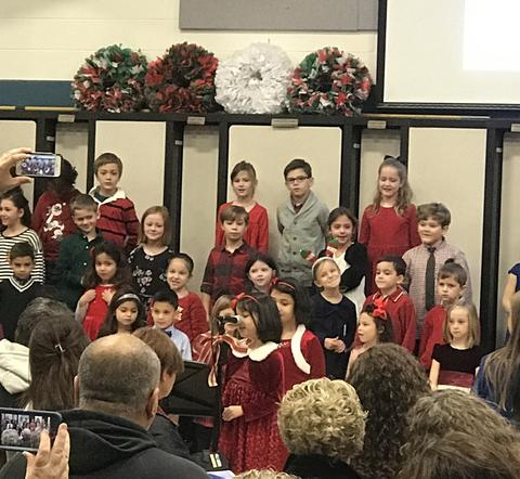 Class performing at a holiday sing with a little girl at the microphone performing a solo