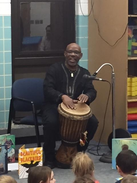 Oba plays his drum and sings