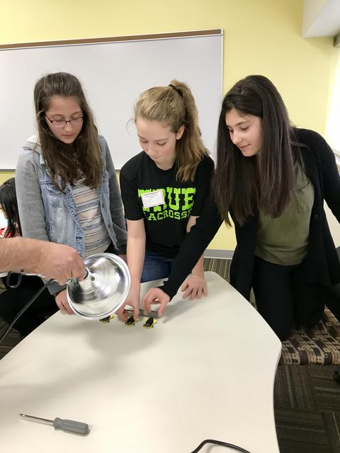 three students with rotobikits under a large light