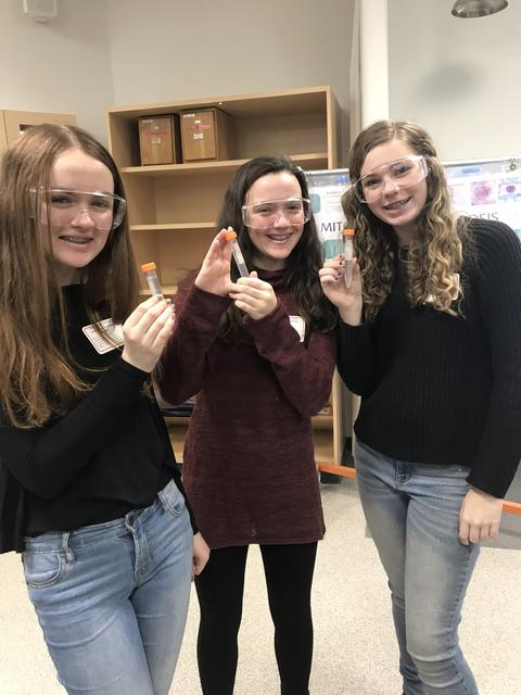 three girls holding test tubes and wearing goggles