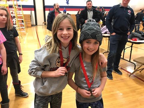 Two girls showing off their medals