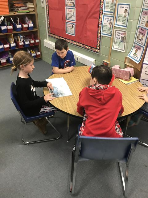 Students gathered around a round table reading a book together.