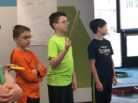 Three students standing in front of room for presentation