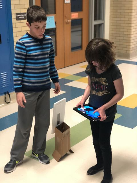 Two students using iPad in hall