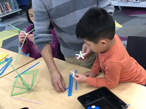student working with and adult constructing structure out of straw
