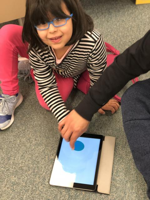 girl working on ipad with help from an adult
