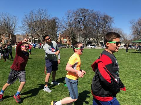 Runners going by teacher wearing sunglasses