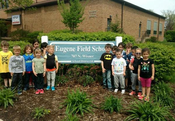 preschool students standing by Field school sign
