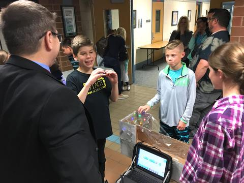students explaining project to Dr. Morrison