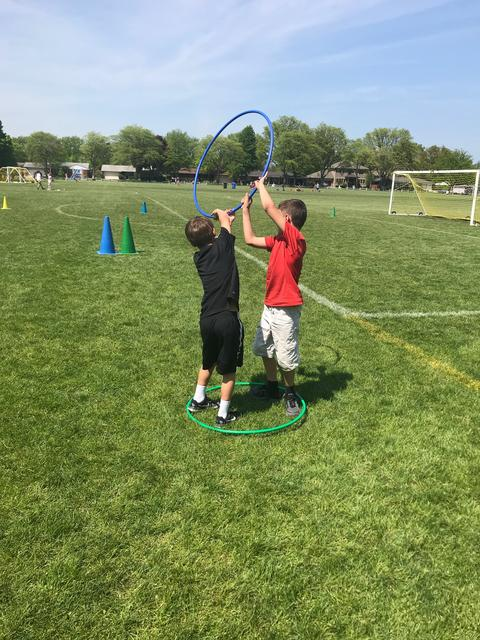 boys working a hula hoop at field day
