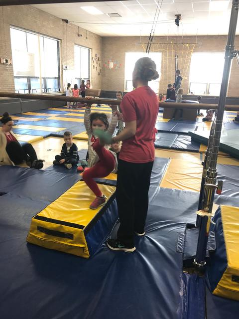 Teacher with girl on parallel bars