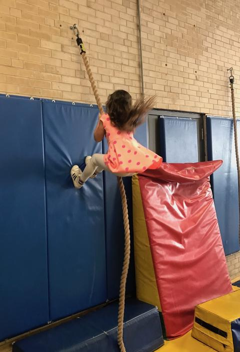 girl climbing wall with rope