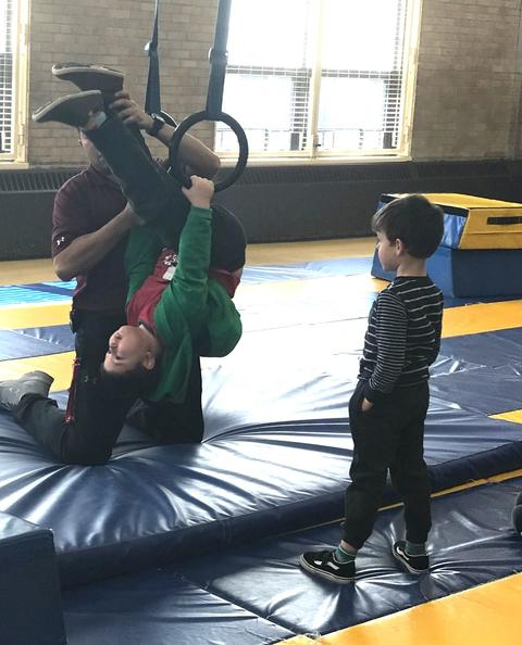 teacher helping boy flip using rings
