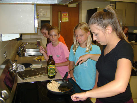 students stirring contents of a pan