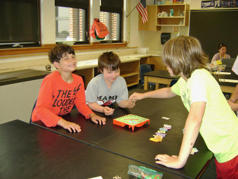 three boys playing a table game