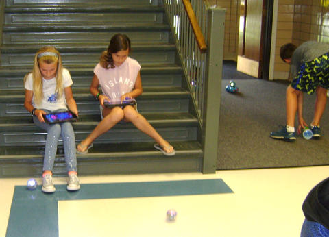 girls sitting on steps using ipads to operate Osmos