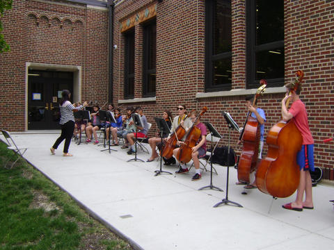 teacher conducting orchestra outside