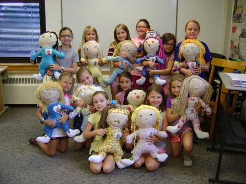 Students holding ME Dolls