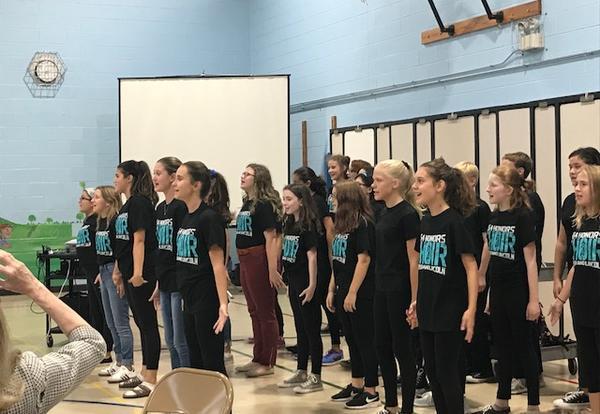 chorus performing at board meeting