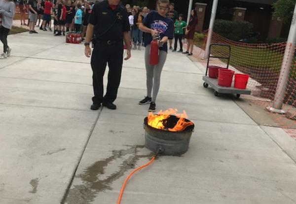 student and fireman with extinguisher
