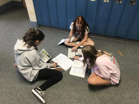 three students working on floor in corridor