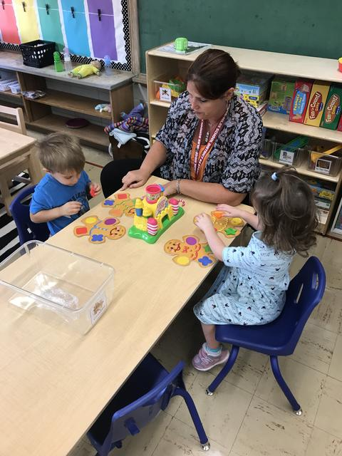 Pre-k students working with teacher and play dough