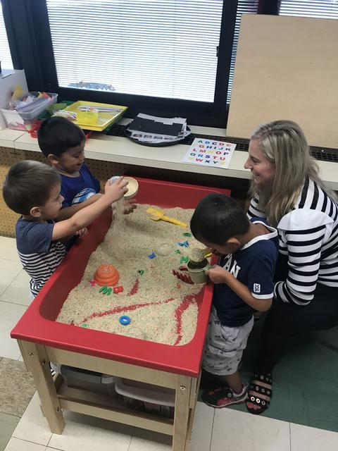 Pre-k students playing at sand table