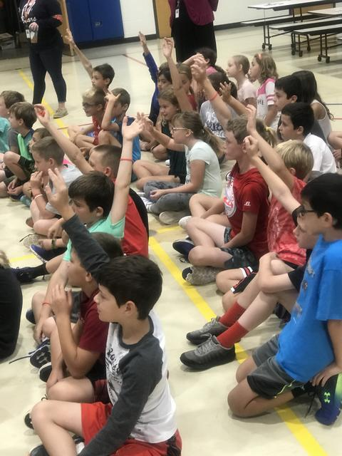 students sitting on floor raising hands