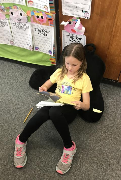 girl reading in comfy floor chair