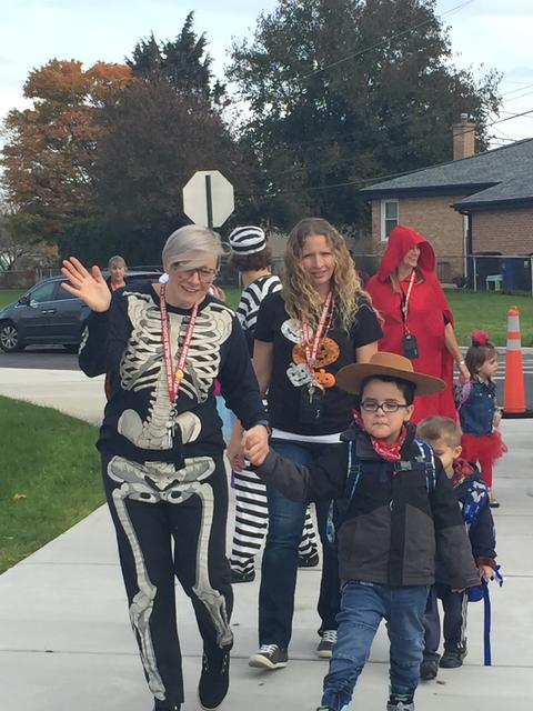 Skeleton and cowboy walk hand in hand for Halloween